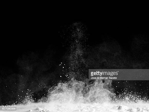 Explosion particles of white powder on a black background