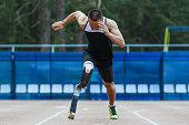 Explosive start of man athlete amputee at stadium. running at a sprint distance
