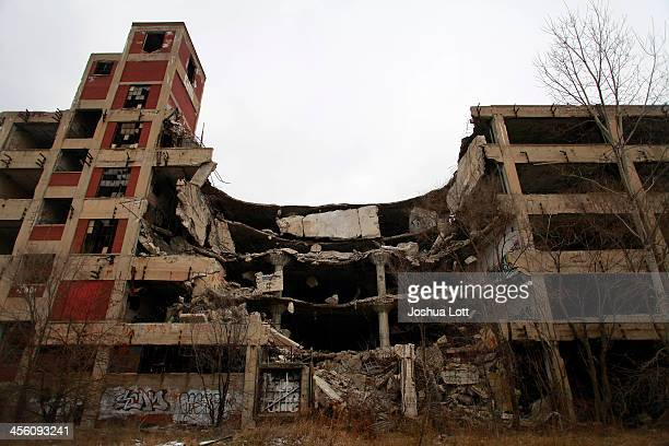 Exposed rebar and concrete chunks hang from the abandoned Packard Automotive Plant December 13 2013 in Detroit Michigan Perubased developer Fernando...