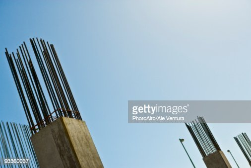 Exposed rebar protruding from unfinished concrete column against blue sky, low angle view
