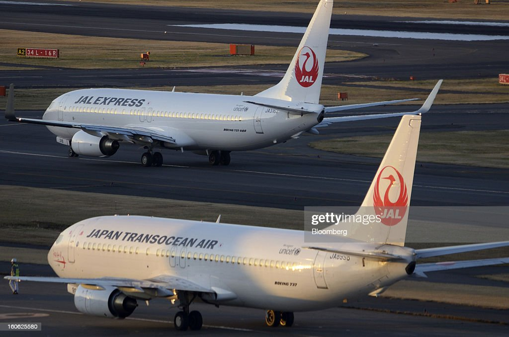 Express Boeing Co. 737 aircraft operated by Japan Airlines Co. (JAL), top, and a Japan Transocean Air Boeing Co. 737 aircraft operated by Japan Airlines Co. (JAL)line up on the runway prior to taking off at Haneda Airport in Tokyo, Japan, on Sunday, Feb. 3, 2013. Japan Airlines, the nation's largest carrier by market value, is scheduled to release earnings on Feb. 4. Photographer: Akio Kon/Bloomberg via Getty Images