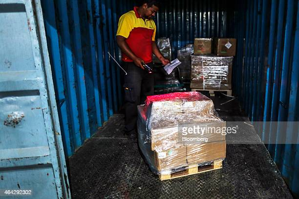 Express India Pvt employee scans a package at the company's joint hub with Blue Dart Express Ltd in Cargo Terminal 3 at Bengaluru International...