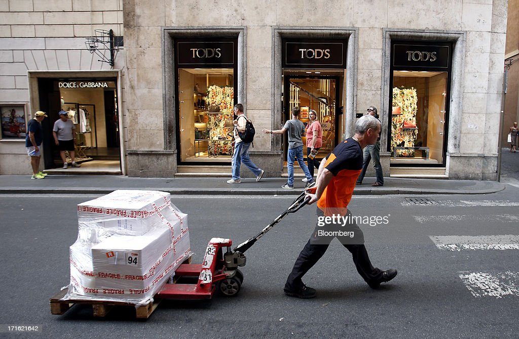 Express NV courier pulls a pallet truck laden with goods as he passes a Tod's SpA store on Via Condotti in Rome, Italy, on Wednesday, June 26, 2013. Italian household confidence rose this month as consumers grew optimistic about the country's outlook as Prime Minister Enrico Letta's government plans to cut taxes and boost youth employment. Photographer: Alessia Pierdomenico/Bloomberg via Getty Images