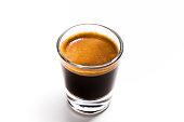Close up fresh hot coffee view in a shot glass.