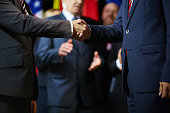 Two politicians handshaking on background of applauding delegates