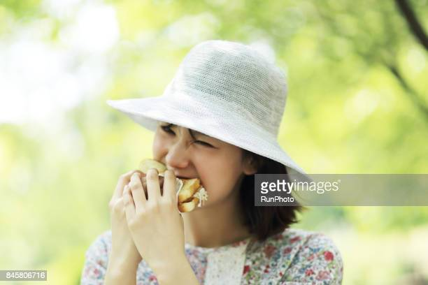 expression of a woman who is closing his eyes and holding bread