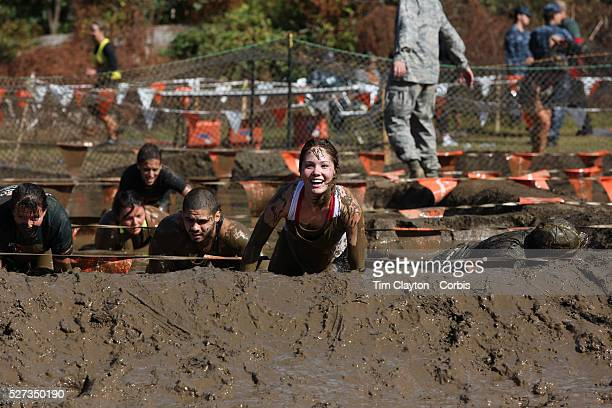 Expressions of competitors as they tackle the mud pit during the New York Merrell Down and Dirty Obstacle Race presented by Subaru Over 6000...