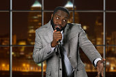 Expressive black man with microphone. Stand-up comedian on night background. Comedy show on local television. Old funny story.