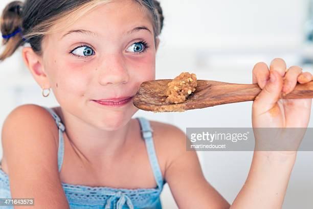 Ausdrucksstarke kleines Mädchen isst cookie-Teig und lieben es!