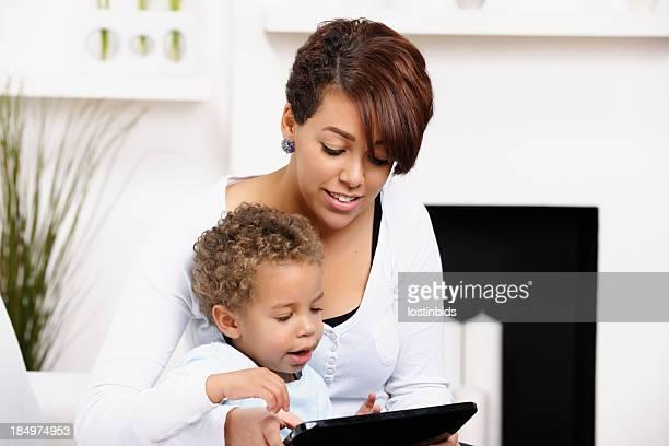 Expressif bébé et jeune maman et sœur à l'aide d'une tablette numérique