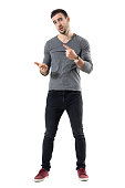 Expressive young casual man explaining and gesticulating with hands. Full body length portrait isolated over white studio background.