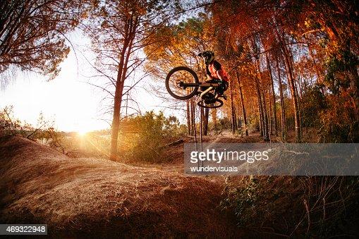 Exteme mountain biker performing aerial maneuvers while dirt jum