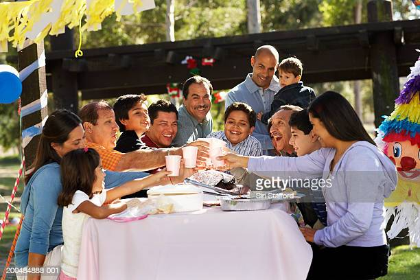 Extended family having toast in park