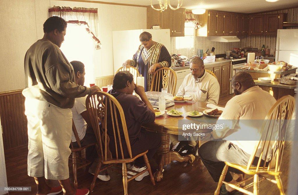 Extended family praying before dinner : Stock Photo