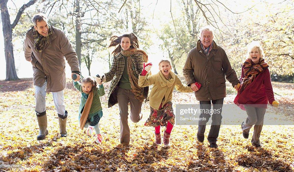 Extended family running in park in autumn