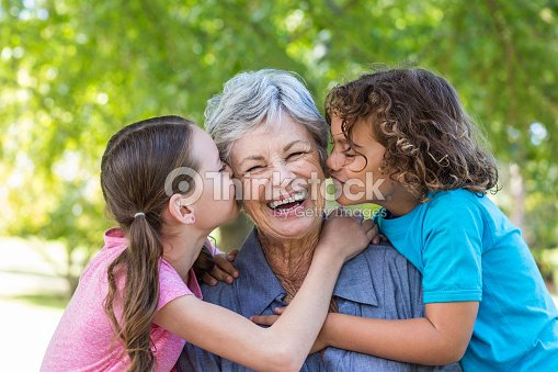 Extended family smiling and kissing in a park : Stock Photo