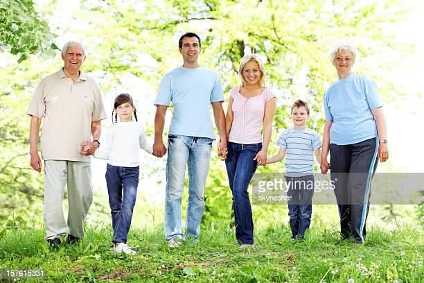 Estesa famiglia felice a piedi nel parco.