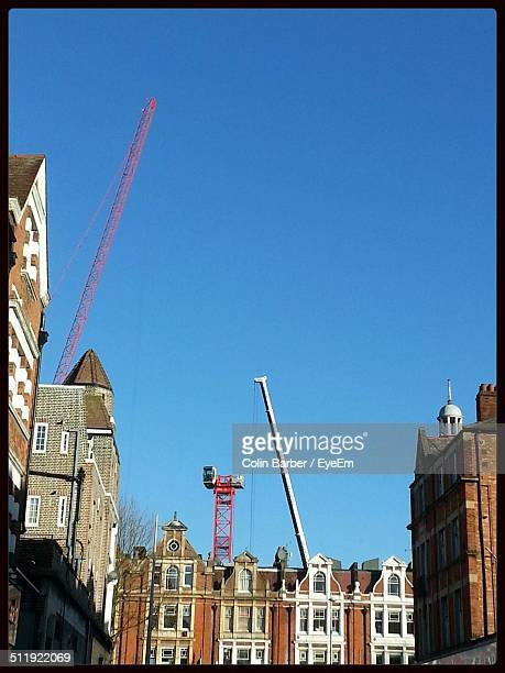 Exterior of building and cranes against clear blue sky