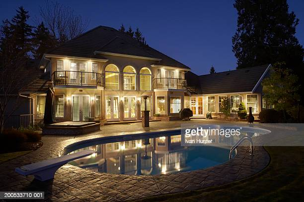 Exterior of house and swimming pool illuminated at dusk