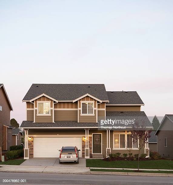 Exterior of house with car parked in driveway, sunset