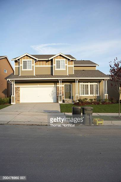 Exterior of house with garbage and recycling bins at end of driveway