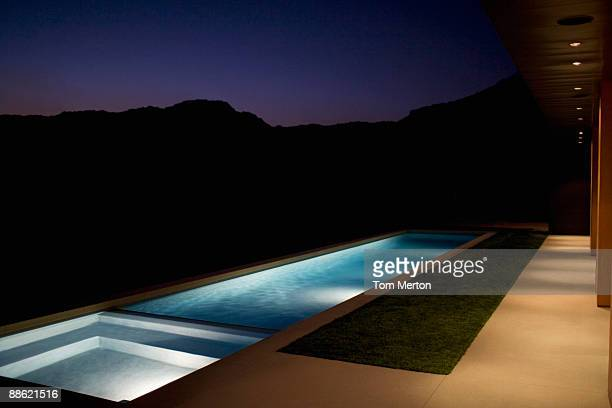 Exterior of modern house and swimming pool at night