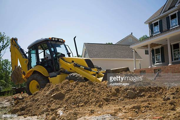 Exterior of unfinished house with tractor