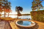 Exterior of waterfront house with jacuzzi at the back yard and perfect water view at sunset.  Northwest, USA