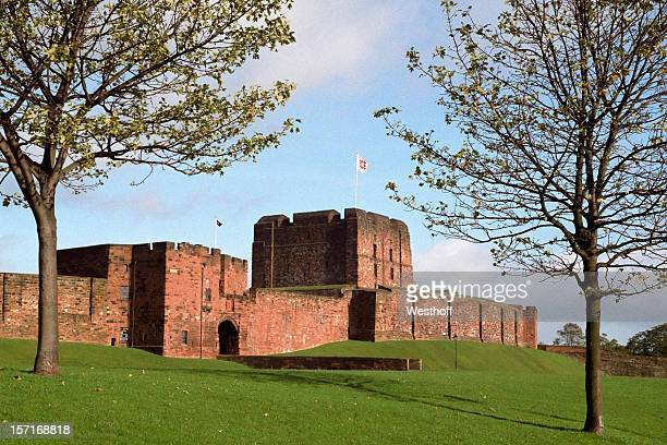 Exterior view of Carlisle Castle with green grass and sky