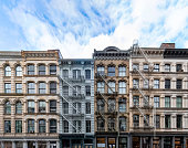 Exterior view of old apartment buildings in the SoHo neighborhood of Manhattan in New York City with empty blue sky background overhead