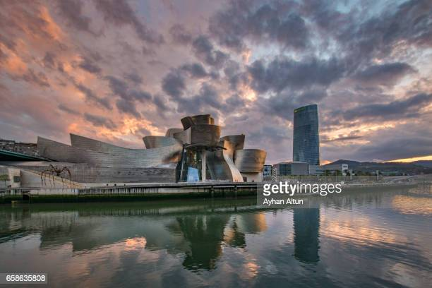 Exterior view of The Guggenheim Museum along the Nervion river at sunset,Basque Country,Spain
