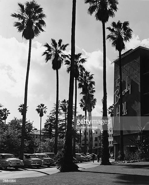Exterior view of the landmark Beverly Hills Hotel with tall palm trees and cars parked in front of the hotel California circa 1950s