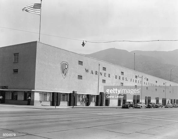 Exterior view of the long concrete building housing Warner Bros First National Pictures Los Angeles California A US flag flies from the corner of the...