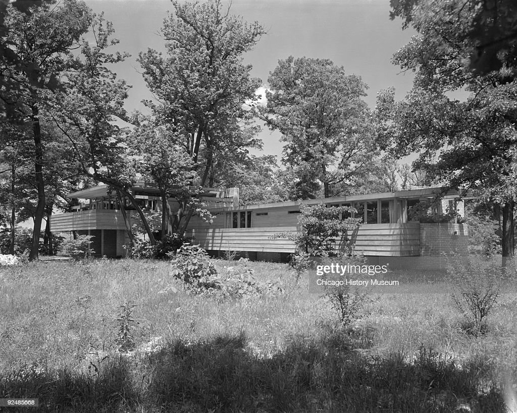Exterior view showing front elevation of the Lloyd Lewis house, a two-story, brick and wood dwelling situated on a wooded lot on the banks of the Des Plaines River at 153 Little Saint Mary's Road in Libertyville, IL, July 1941. The structure was designed by Frank Lloyd Wright.