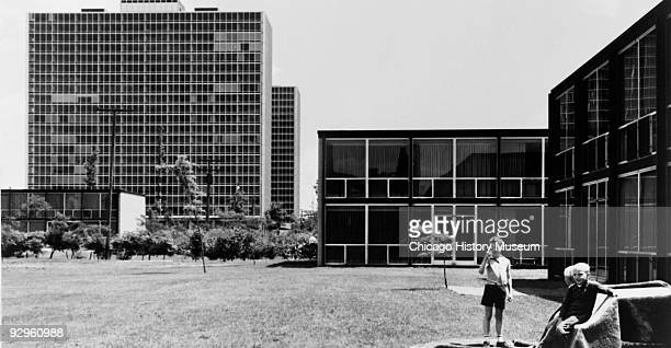 Exterior view showing lawn with children and lowrise building in foreground highrise buildings in background part of the Lafayette Park development...
