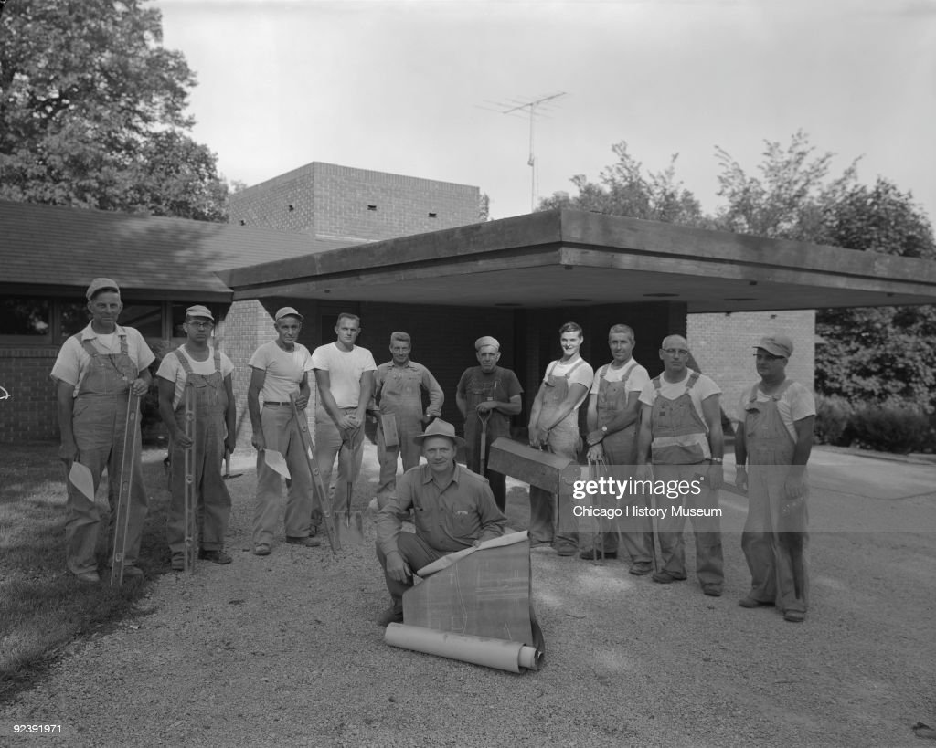 Exteriors of the Carroll Alsop residence at 1907 A Avenue East in Oskaloosa (Iowa), designed by Frank Lloyd Wright, July 1958. Image shows unidentified construction workers holding blueprints in front of the carport.
