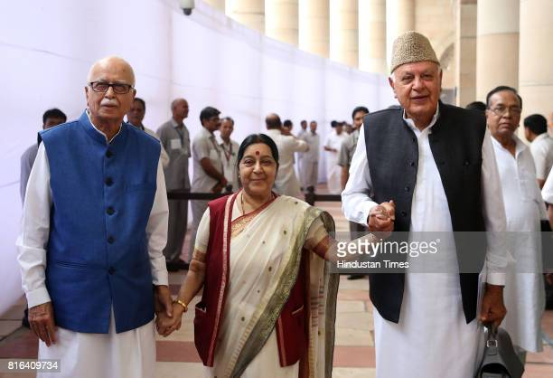 External Affairs Minister Sushma Swaraj holds the hands of Senior BJP leader LK Advani and President of National Conference Farooq Abdullah after...