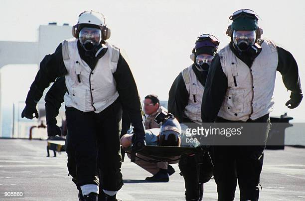 External litter bearers with Chemical Biological and Radiological lothing and MCU2P gas masks carry a 'patient' from a helicopter to one of the...