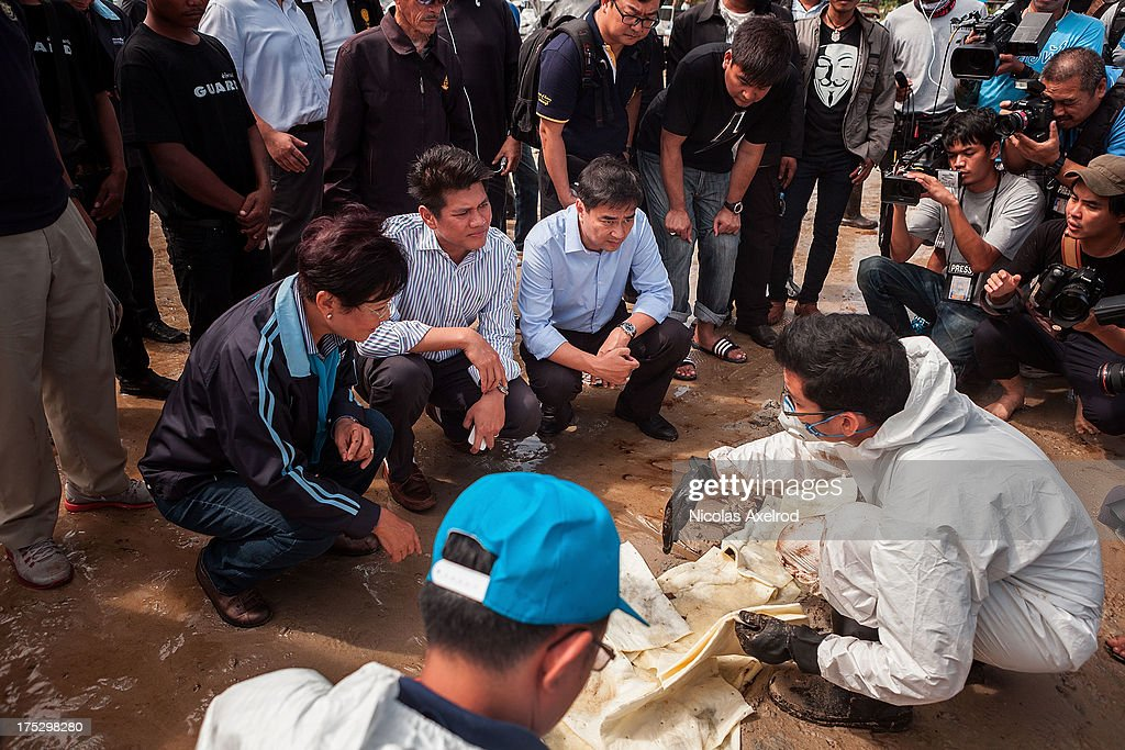 Ex-Thai Prime Minister Abhisit Vejjajiva talks to members of a team who have been tasked with the clean up of an oil spill that washed up on Koh Samed, an island in the south of Thailand with relies mainly on tourism for income, on August 2, 2013 in Koh Samed, Thailand. An oil leak from a pipeline run by the Thai oil company PTT spilt more than 50 000 litres of oil into the Gulf of Thailand. It is still unclear the extent of the damage caused to marine life, local fishermen and tourism on August 2, 2013 in Koh Samed, Thailand.
