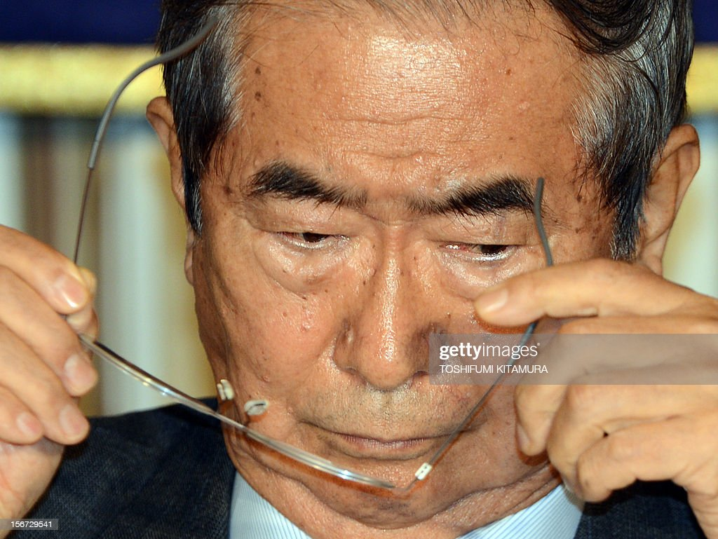 Ex-Tokyo governor Shintaro Ishihara puts on his glasses during his FCC professional luncheon in Tokyo on November 20, 2012. Controversial ex-Tokyo governor Shintaro Ishihara addressed foreign media after joining forces with Osaka mayor Toru Hashimoto to forge a 'third force' ahead of snap general elections. AFP PHOTO / TOSHIFUMI KITAMURA