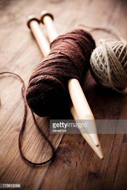 Extra large knitting needles piercing a skein of brown wool