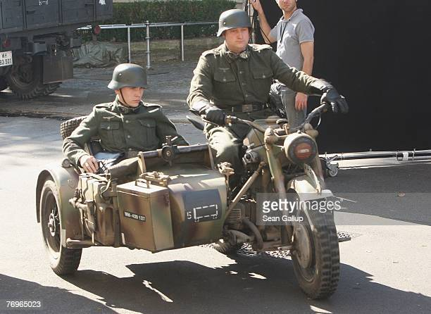 Extras wearing World War IIera German military uniforms drive a motorcycle and sidecar near the set of 'Valkyrie' outside the Bendler Block September...