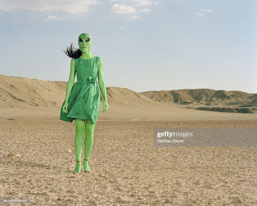 Extraterrestrial wearing green dress standing in desert