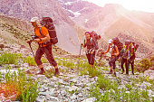 Group people approach high altitude mountain climbing camp with heavy backpacks tons alpine gear walking on rocky path trail at peaks glaciers snow sun sky background
