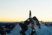 Young brave man alpinist standing on mountain top