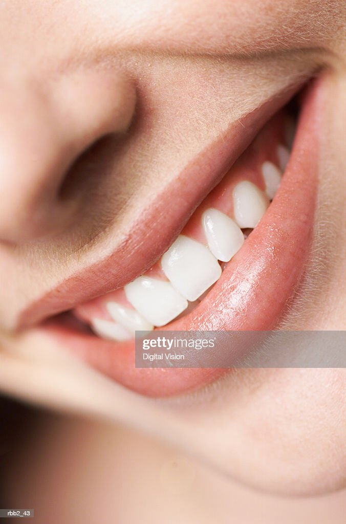 extreme close up of a young caucasian girls pearly white teeth as she smiles