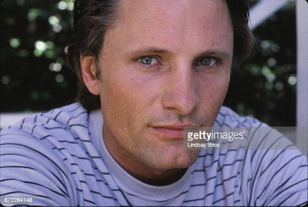 Extreme closeup view of Viggo Mortensen wearing a light blue tee with navy pinstripes as he sits on a porch and peers into the lens during a photo...