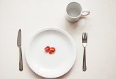 white background of a meal that consists of a small tomato.  high contrast between subject and background. unhealthy diet with low calories. cup, fork, spoon, plate with a slice of tomato, anorexia,