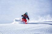 Expert backcountry skier going fast through fresh powder snow