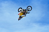 Extreme motocross rider perfoming backflip in mid air